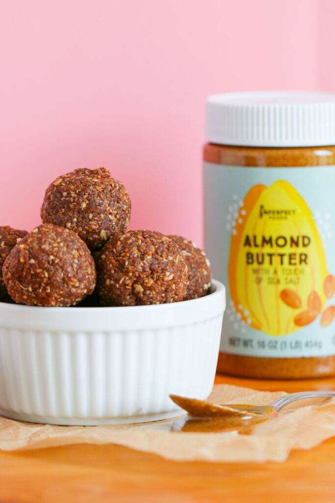 Bowl of almond butter energy balls with jar of Imperfect foods almond butter
