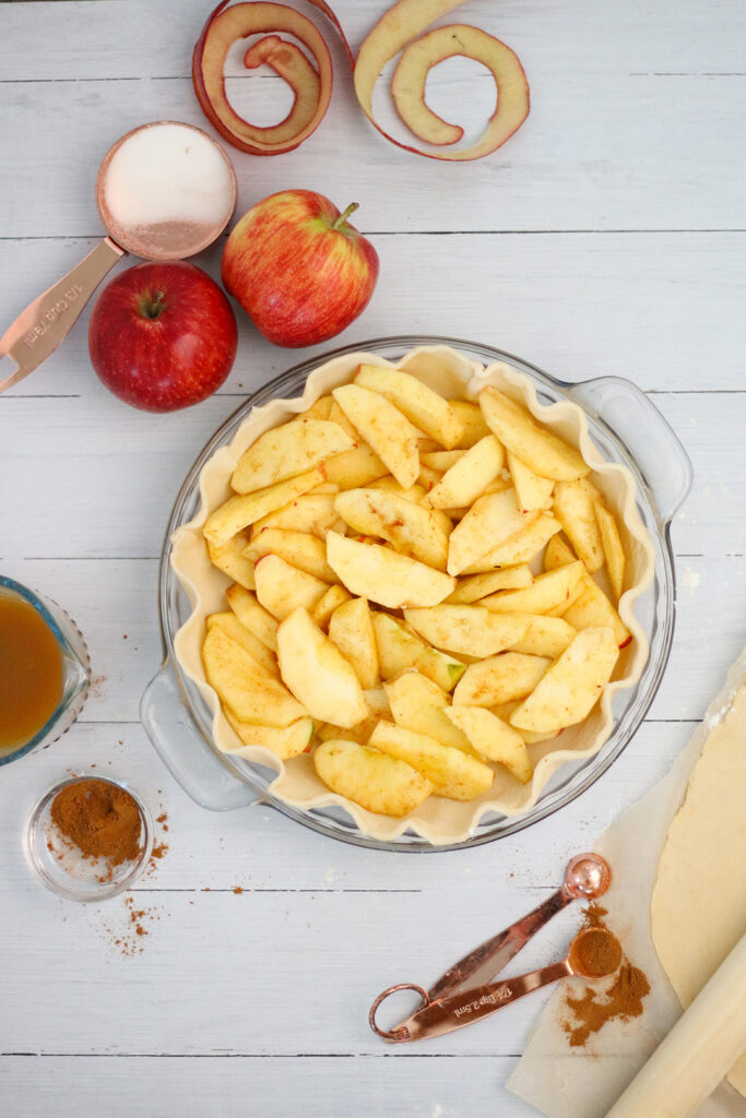 Filling up the pie with apples sprinkled with cinnamon